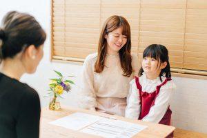 東京ルクスピアノ教室の無料体験レッスン風景 子どもと親が講師とラウンジスペースで笑顔で話をする様子|東京のピアノ教室 東京ルクスピアノ教室