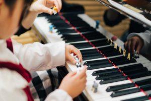 東京ルクスピアノ教室の無料体験レッスン風景 子どもと講師がグランドピアノでドの音に人形を置いている様子|東京のピアノ教室 東京ルクスピアノ教室