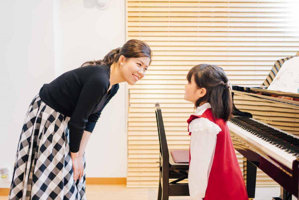 東京ルクスピアノ教室の無料体験レッスン風景 子どもと講師がグランドピアノの前で挨拶をする様子|東京のピアノ教室 東京ルクスピアノ教室